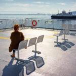 Une femme assise de dos sur un banc prête à partir en voyage